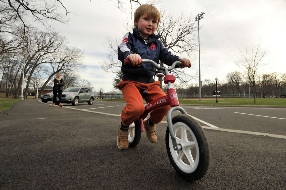 Adam Tuma, 4, rides his balance bike as his mother, Radka Tumova, watches in the background at Scalzi Park in Stamford, Conn., on Thursday, April 16, 2015. Gov. Dannel P. Malloy has a proposal to expand bike lanes and trails throughout the state. Photo: Jason Rearick / Stamford Advocate