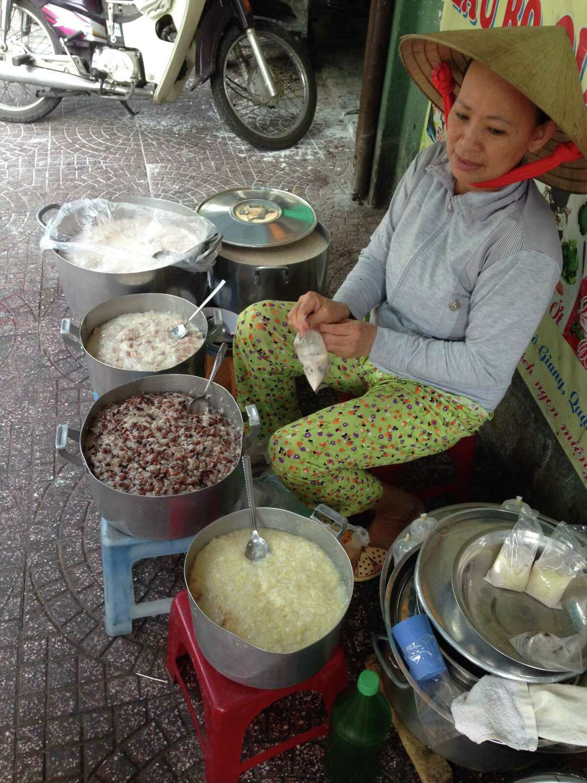 A woman sells three types of rice porridge on the streets of Ho Chi Minh City, Vietnam.