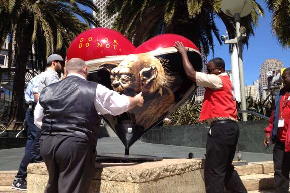 Workers put the toppled Yoda back into place at the edge of Union Square