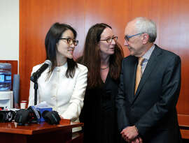 Ellen Pao talks to reporters as her lawyers Therese Lawless and Alan Exelrod stand behind her.