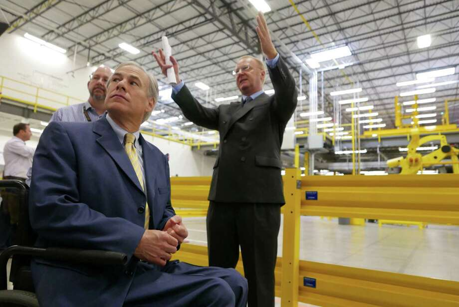 Texas Governor Greg Abbott, left, takes a tour guided by Mike Roth, vice president of North American operations for Amazon, at the new Amazon Fulfillment Center in Schertz, Texas, on Friday, April 17, 2015. Photo: Billy Calzada, Staff / San Antonio Express-News /  San Antonio Express-News
