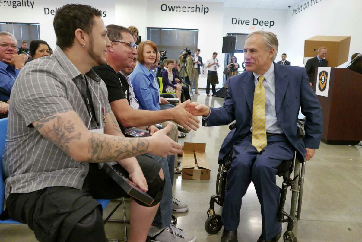 Texas Governor Greg Abbott greets veterans attending the grand opening of the new Amazon Fulfillment Center in Schertz, Texas, on Friday, April 17, 2015.