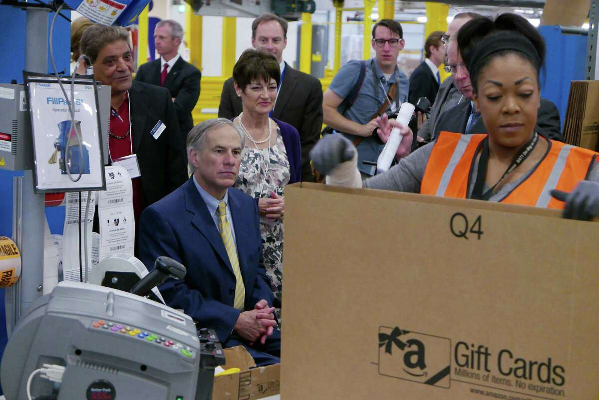 Texas Governor Greg Abbott observes worker Jenae Dillon at the grand opening of the new Amazon Fulfillment Center in Schertz, Texas, on Friday, April 17, 2015.