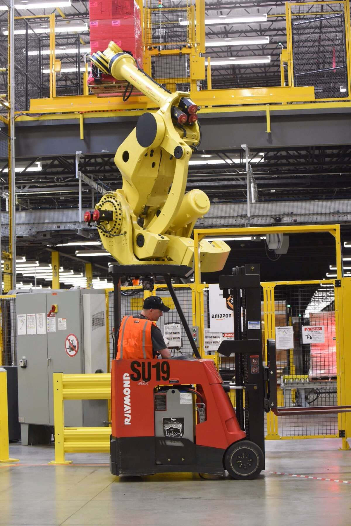 An Amazon employee works by a large robotic arm at the new Amazon Fulfillment Center in Schertz, Texas, on Friday, April 17, 2015.