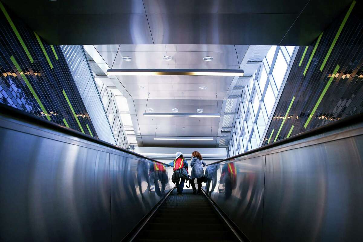 People ride an escalator out of Sound Transit's nearly completed University of Washington Station.