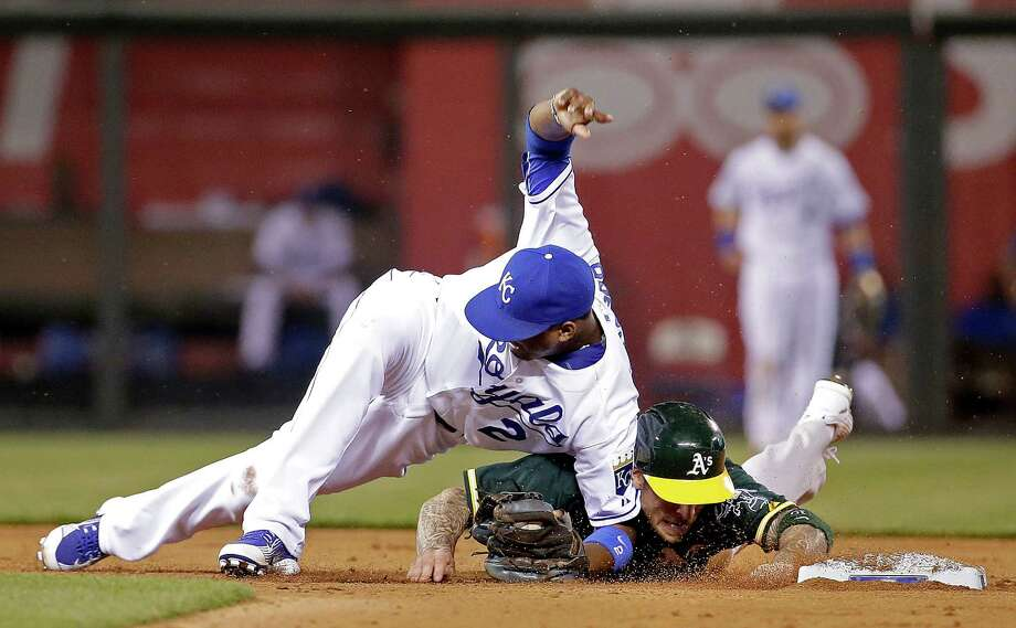 Kansas City Royals shortstop Alcides Escobar (2) and Oakland Athletics' Brett Lawrie become entangled after Lawrie was forced out during the seventh inning of a baseball game Friday, April 17, 2015, in Kansas City, Mo. (AP Photo/Charlie Riedel) Photo: Charlie Riedel / Associated Press / AP