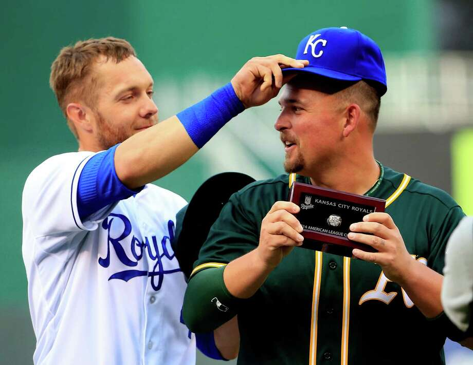 Alex Gordon (left) of the Royals switches hats with former teammate Billy Butler, now with the A's, during a pregame ceremony to present the longtime Kansas City player with his American League Championship ring for last October. Photo: Jamie Squire / Getty Images / 2015 Getty Images