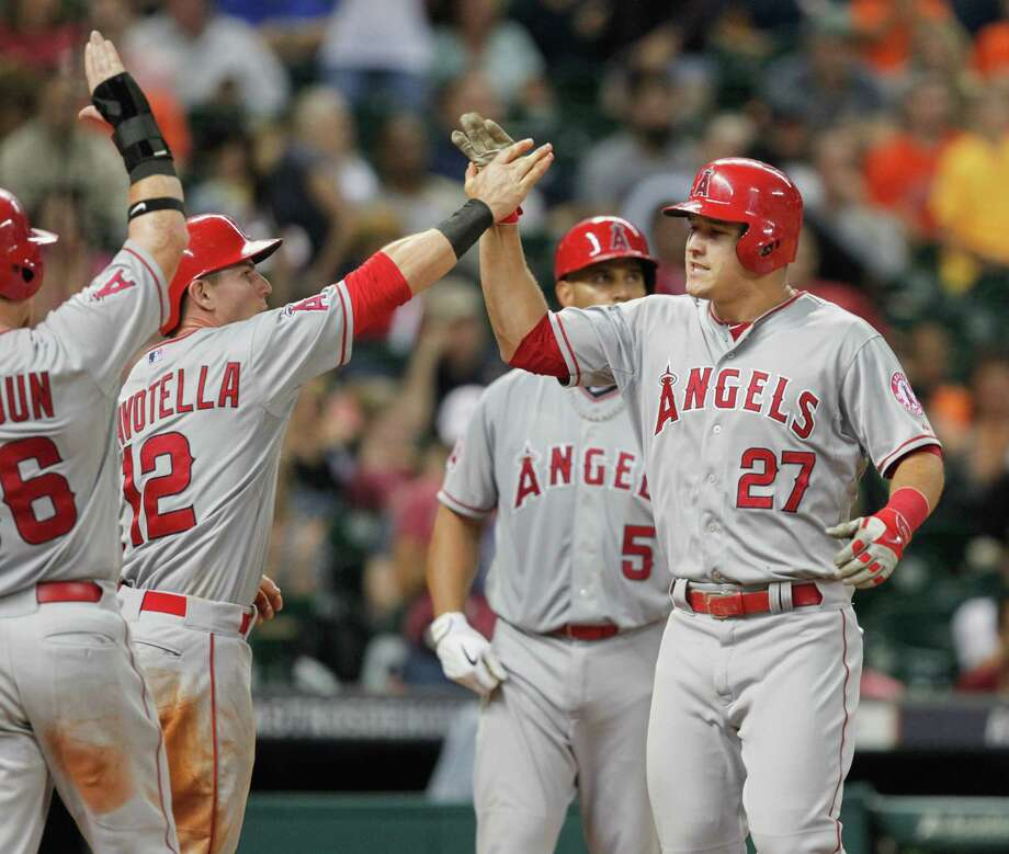 HOUSTON, TX - APRIL 17:  Mike Trout #27 of the Los Angeles Angels of Anaheim receives a high five from Johnny Giavotella #12 and Kole Calhoun #56 after hitting a three run home run in the eighth inning against the Houston Astros at Minute Maid Park on April 17, 2015 in Houston, Texas.  (Photo by Bob Levey/Getty Images) Photo: Bob Levey, Stringer / Getty Images / 2015 Getty Images