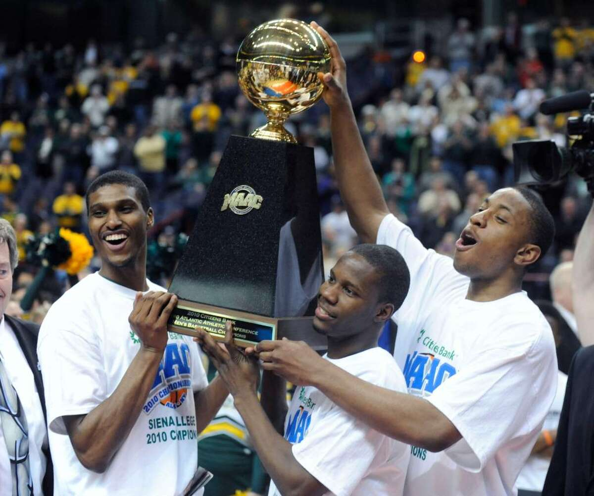 Siena players Edwin Ubiles, left, Ronald Moore, center, and Alex Franklin, right, hold their trophy after beating Fairfield 72-65 in the championship game of the NCAA Metro Atlantic Athletic Conference men's college basketball tournament in Albany, N.Y., on Monday, March 8, 2010. From left are Edwin Ubiles (AP Photo/Tim Roske)