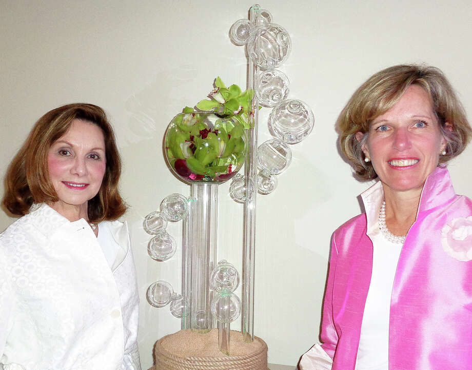 Andrea Hoffman, left, and Fleur Rueckert, co-chairwomen of the Fairfield Garden Club's Centennial Flower Show, pose in front of one of the more than 100 entries in the show. Fleur, French for flower, said her love for flowers was not influenced by her name but rather by ìmy mother.î Photo: Meg Barone / Fairfield Citizen