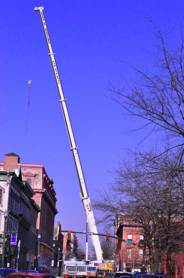 A crane lifts HVAC equipment to th roof of the Quakenbush building on Saturday, April 18, 2015 on Broadway in Troy, N.Y.  (Steve Barnes/Times Union)