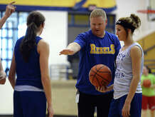 Blake Gravis, left, and Hannah Oldbury, right, listen as coach Robert Hollyfield, center, gives some instruction Wednesday. The Evadale High School girls basketball team practiced Wednesday afternoon. Photo taken Wednesday, 1/15/14 Jake Daniels/@JakeD_in_SETX