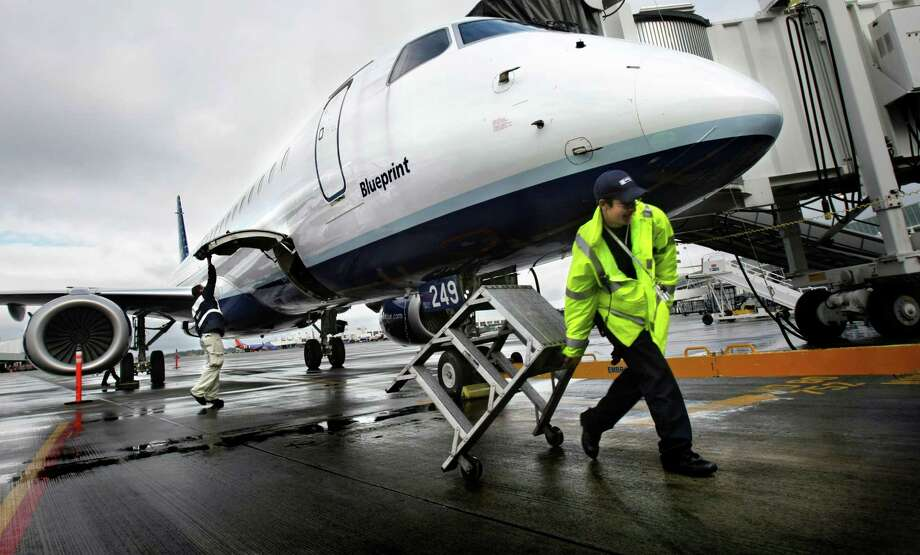Esteban Rendon removes a step stool from below the JetBlue Airways EMBRAER E190 airplane that was fueling in preparation for a flight from Seatac International Airport back to Long Beach, Calif. Monday, April 7, 2008. (AP Photo/Seattle Post-Intelligencer, Andy Rogers) Photo: Andy Rogers / AP2008