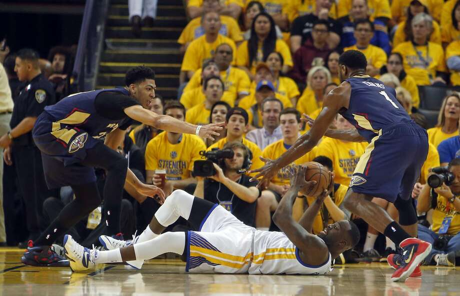 Golden State Warriors' Draymond Green looks to pass from the floor while being defended by New Orleans Pelicans' Anthony Davis and Tyreke Evans in 2nd quarter during Game 1 of the 1st Round of NBA Western Conference Playoffs at Oracle Arena in Oakland, Calif., on Saturday, April 18, 2015. Photo: Scott Strazzante, The Chronicle