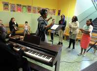 Linda Mitchell leads the Giffen Outreach Community Chorus as part of Authors & Illustrators Day at Giffen Memorial Elementary School on Saturday April 18, 2015 in Albany, N.Y. (Michael P. Farrell/Times Union)