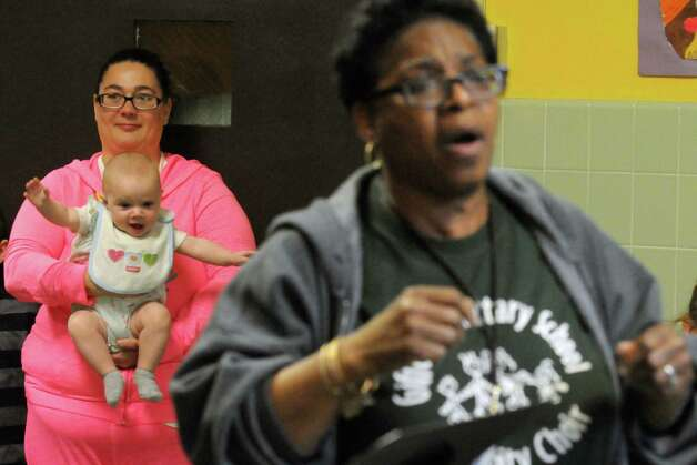 Five-month-old Saphire Lawerance, held by Stepanie Willsey bops about to the Giffen Outreach Community Chorus leasd by Linda Mitchell as part of Authors & Illustrators Day at Giffen Memorial Elementary School on Saturday April 18, 2015 in Albany, N.Y. (Michael P. Farrell/Times Union) Photo: Michael P. Farrell / 00031491A