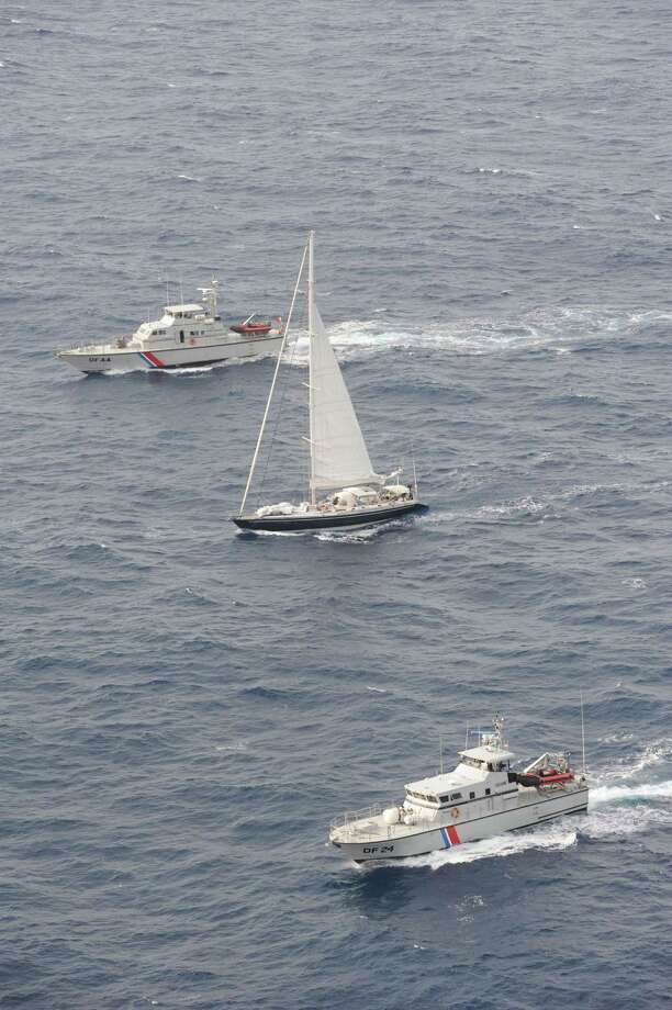 A handout photo taken on April 16, 2015 by the French customs off the French Caribbean island of Martinique, and released on April 18, shows the Silandra sailboat (C) carrying cocaine escorted to Fort-de-France by two customs vessels after the boat's interception on April 15 in the night. French finance minister Michel Sapin announced on April 18 a record seizure on the boat of 2.25 tonnes of cocaine, worth 70 millions of euros. Three Spanish nationals and a Venezuelan national were arrested on the boat. AFP PHOTO/DOUANE FRANCAISE-/AFP/Getty Images Photo: - / AFP / Getty Images / AFP