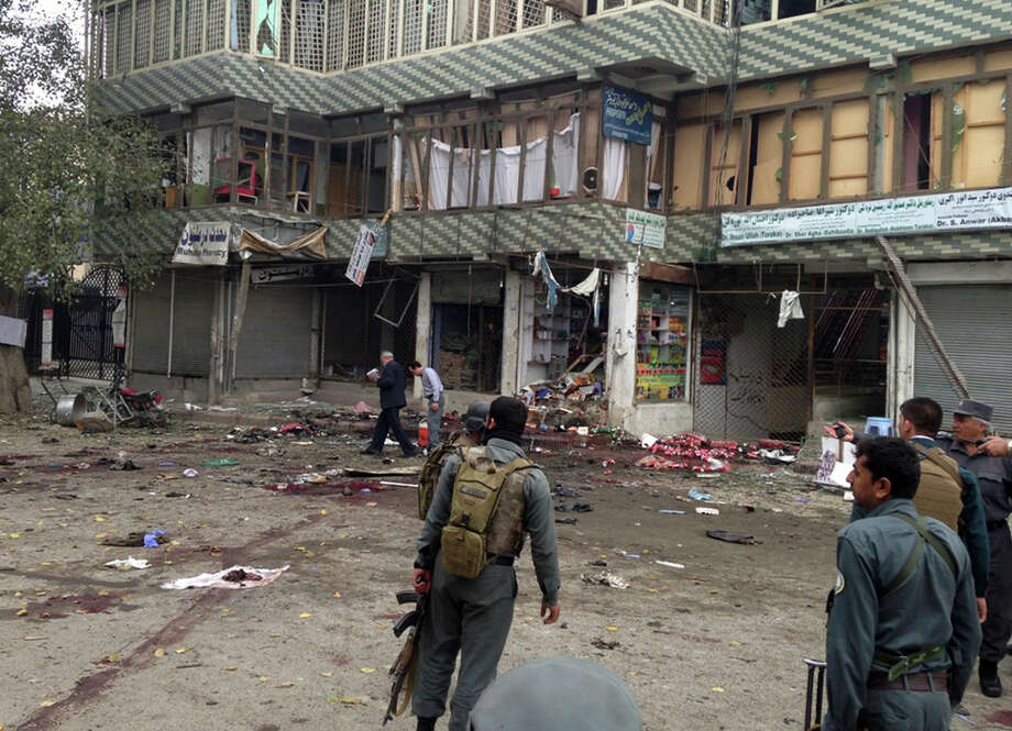 Afghan security forces inspect the site of a suicide attack near a bank branch in Jalalabad. Photo: Associated Press / AP