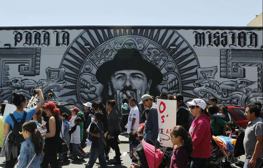 A group of people walk past a mural near the corner of 19th and Mission Streets during the Cesar Chavez Day Parade in the Mission District of San Francisco, Calif. Saturday, April 18, 2015 Photo: Jessica Christian, The Chronicle