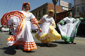 Members of Ensambles Dance Academy walk down Mission Street during the Cesar Chavez Day Parade in the Mission District of San Francisco, Calif. Saturday, April 18, 2015