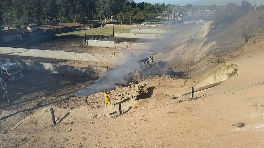 Handout photo dated April 17, 2015 of the blast site at Fresno County Sheriffs firing range at 7633 North Weber Ave. PG&E officials, who provided the photo, say it shows a sign (left, center) warning of the presence of an underground natural gas line. At the center of the photo is the burned out front-end loader that triggered the explosion. At right is an exposed part of the gas pipeline. Photo: Courtesy Of PG & E, Pacific Gas And Electric
