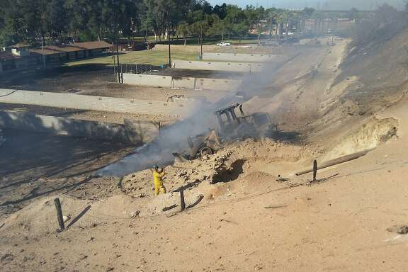 Handout photo dated April 17, 2015 of the blast site at Fresno County Sheriffs firing range at 7633 North Weber Ave. PG&E officials, who provided the photo, say it shows a sign (left, center) warning of the presence of an underground natural gas line. At the center of the photo is the burned out front-end loader that triggered the explosion. At right is an exposed part of the gas pipeline.