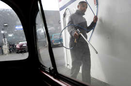 Reggie Ransaw uses a high-pressure spray gun on his 1966 VW at Golden Coin Car Wash in Oakland last month. Most car washes use recycled water.