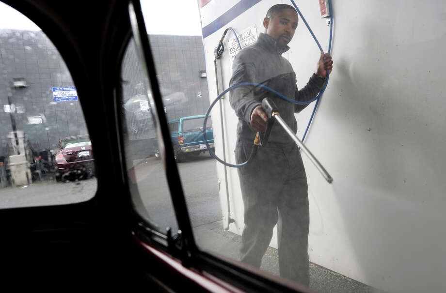 Reggie Ransaw uses a high-pressure spray gun on his 1966 VW at Golden Coin Car Wash in Oakland last month. Most car washes use recycled water. Photo: Michael Short / ONLINE_YES