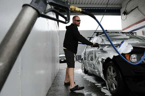 Travis Coffman of Oakland uses a soap brush as he washes his car at the Golden Coin Car Wash in Oakland, CA, on Monday, March 16, 2015.   As California enters it's fourth consecutive year of sever drought plans may be in the works for state wide water restriction laws to be put into place.  Commercial car washes traditionally use less water then you would use washing your car at home by using high pressure hoses and recycling and reusing a portion of the water that otherwise would end up in the street and sewer systems.