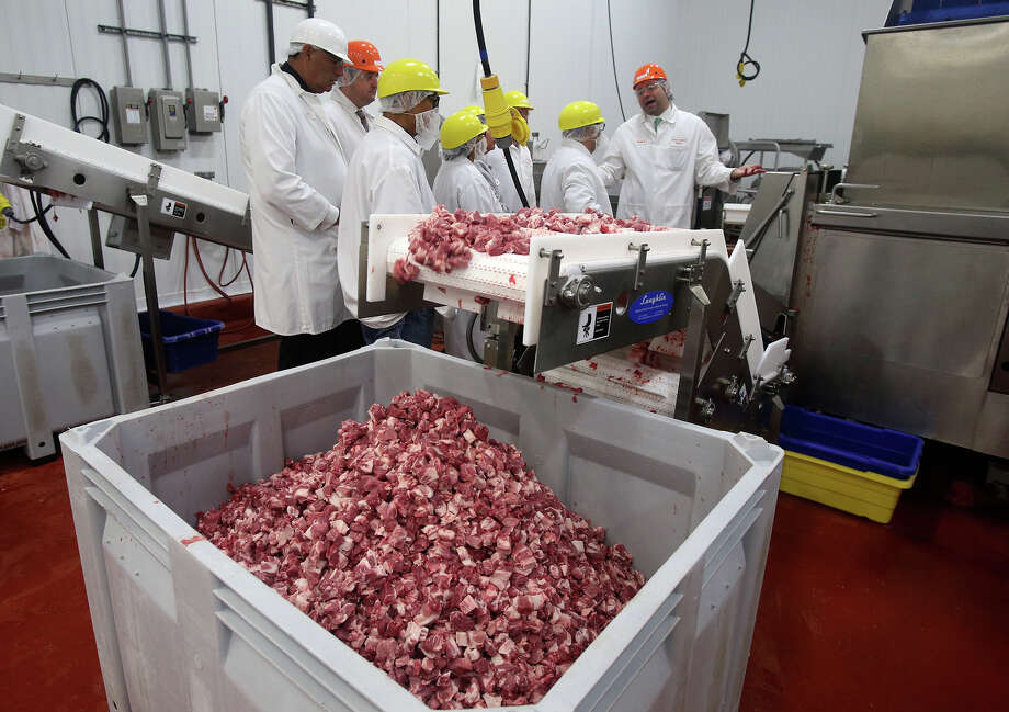 Pork meat cubes fall into a bin Monday April 13, 2015 at Labatt Food Service's Direct Source Meats in San Antonio as a tour is given to people from Native American Indian territories and others. Labatt Food Service is leading an effort to make Navajo and other Native Americans niche players in the beef industry. Photo: John Davenport, Staff / San Antonio Express-News / ©San Antonio Express-News/John Davenport