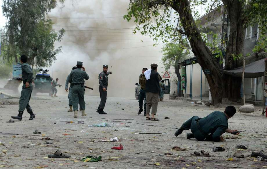 TOPSHOTS Afghan security personnel look on after a second explosion following a suicide attack outside a bank in Jalalabad on April 18, 2015. A suicide bomber killed at least 33 people and wounded 100 others in an attack on April 18 outside a bank in the eastern Afghan city of Jalalabad, provincial officials said. AFP PHOTO / Noorullah ShirzadaNoorullah Shirzada/AFP/Getty Images Photo: NOORULLAH SHIRZADA / AFP