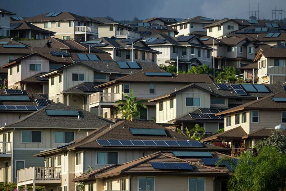 Solar panels cover the rooftops of homes in Kapolei, Hawaii, Feb. 23, 2015. Hawaii has so many homes generating excess solar power that it can cause troubles for a grid designed to carry electricity in the other direction -- one reason some utilities are desperately trying to stem the rise of solar energy. (Kent Nishimura/The New York Times) ORG XMIT: XNYT20 Photo: KENT NISHIMURA / NYTNS