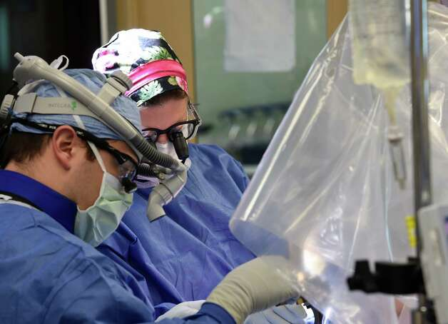 Dr. Alex Riccio, foreground and neurosurgeon Dr. Julie Pilitsis work on patient Tom Bradley during deep brain stimulation surgery at the Albany Medical Center January 29, 2015 in Albany, N.Y.      (Skip Dickstein/Times Union) Photo: SKIP DICKSTEIN / 00030372A