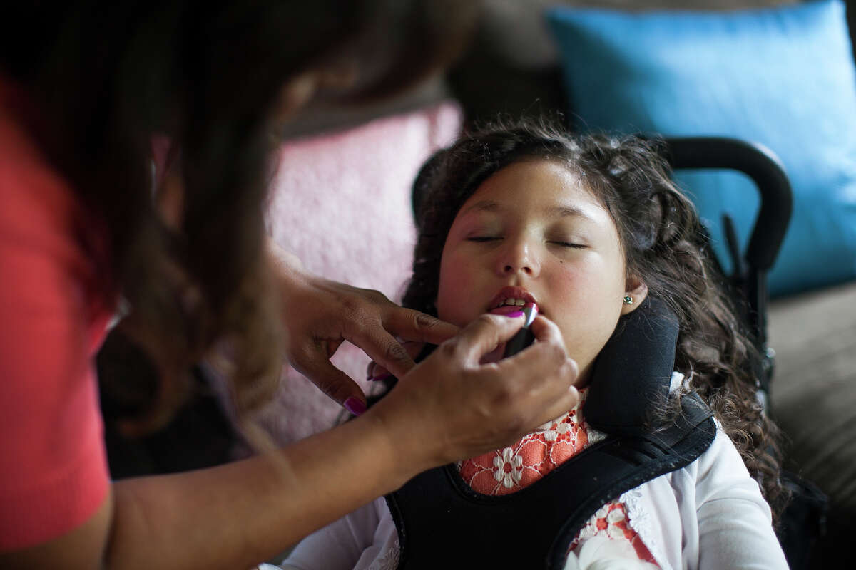 Victoria Ammann applies lipstick to her daughter Emily, 6, while getting ready to attend an ice skating show Friday April 3, 2015. Emily has suffered from seizures since nine weeks old, and her brain is in a constant state of seizing. The non-euphoric cannabidiol oil has proven to treat intractable seizures, and Victoria hopes with the passing of the Texas Compassionate Use Act, House Bill 892 and Senate Bill 339, that Emily can soon receive the same help.