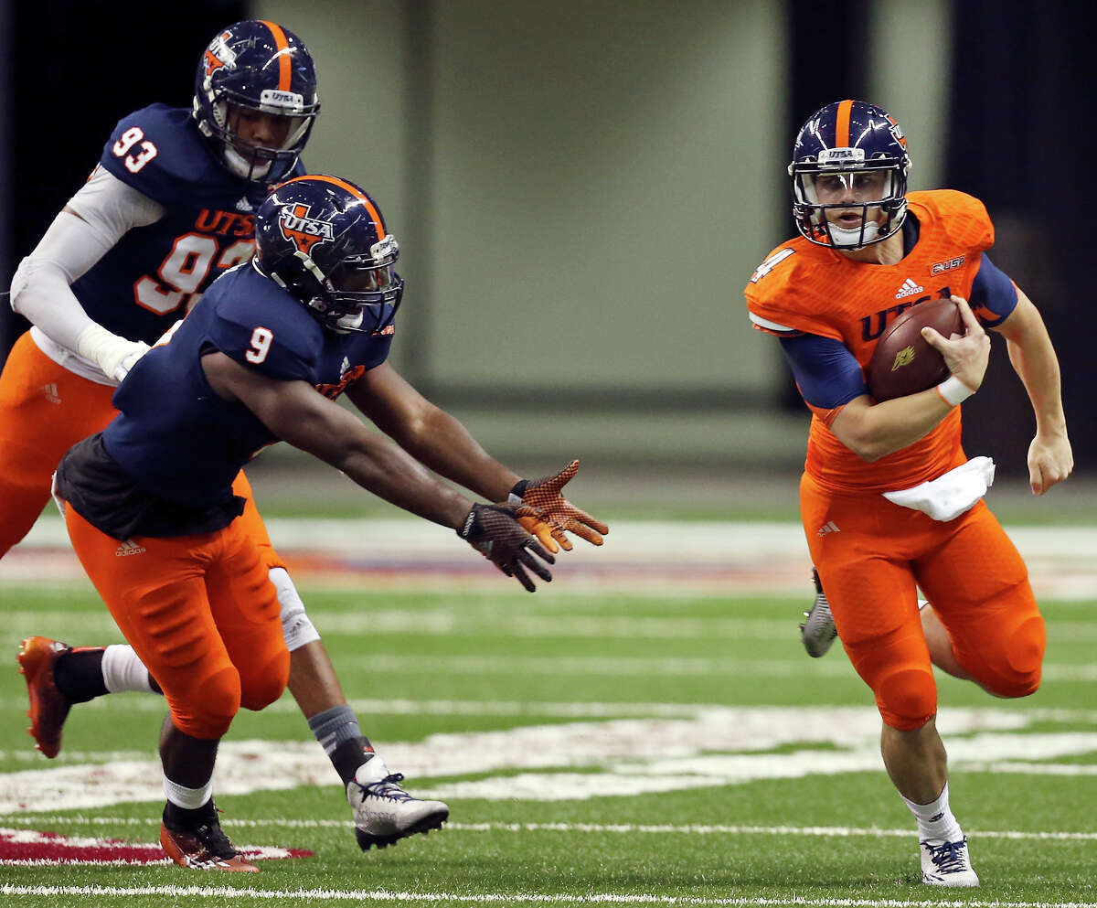 UTSA White Team's Blake Bogenschutz looks for room around UTSA Blue Team's Marcos Curry as Marcus Davenport (rear) moves in on the play during their Football Fiesta Spring Game held Saturday April 18, 2015 at the Alamodome. UTSA White Team won 57-42.