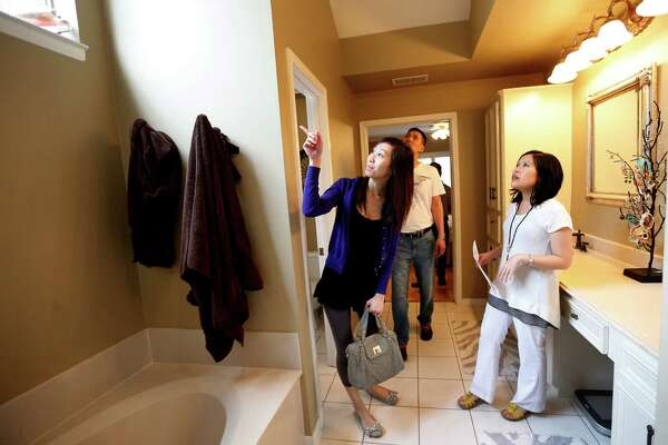 Realtor Julie Tam shows prospective home buyers Andrew Chen, and his fiance Yuki Li a house on Friday, April 3, 2015, in Sugar Land.  Over the past six months, Chen lost out on four houses he tried to bid on previously.