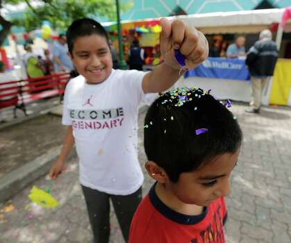Alexander Paz, 12, breaks a cascarone over the head of his little brother, Juan, at Guadalupe Plaza during Pinatas in the Barrio on Saturday, Apr. 18, 2015. Photo: Kin Man Hui, San Antonio Express-News / ©2015 San Antonio Express-News