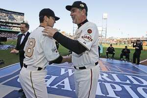 San Francisco Giants' Buster Posey, left, is congratulated by manager Bruce Bochy during the 2014 World Series championship ring ceremony before the team's baseball game against the Arizona Diamondbacks on Saturday, April, 18, 2015, in San Francisco. (AP Photo/Ben Margot, Pool)