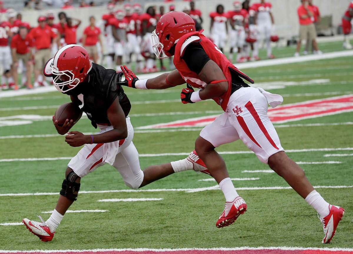 UH quarterback Greg Ward Jr., left, displayed his elusiveness in Saturday's spring game, rushing by safety Earl Foster for a touchdown.