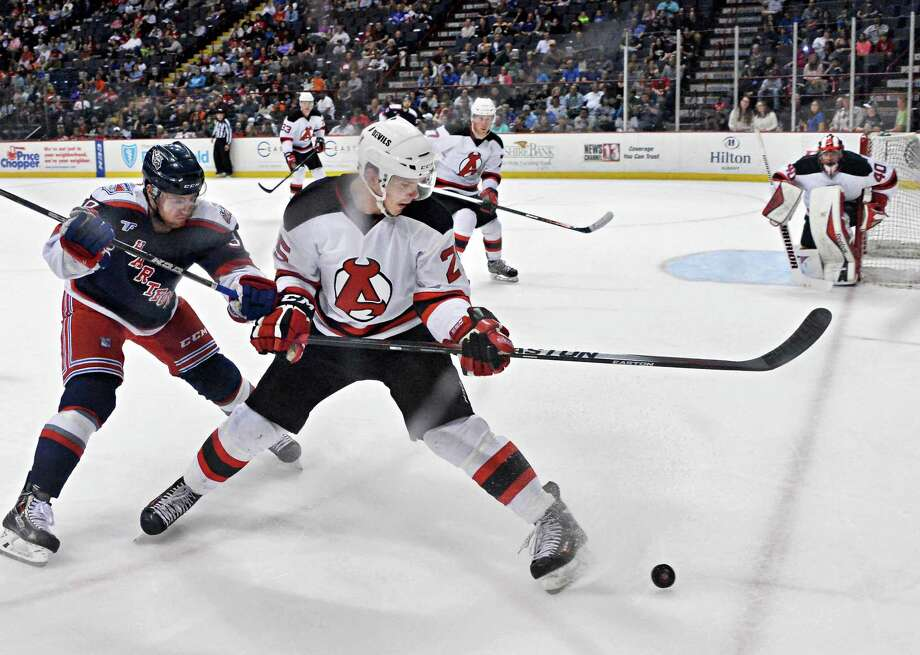 Albany Devils' #25 David Wohlberg battles Hartford Wolfpack's #39 Ryan Haggerty, left, during Saturday's game at the Times Union Center April 18, 2015 in Albany, NY.  (John Carl D'Annibale / Times Union) Photo: John Carl D'Annibale / 00030124T