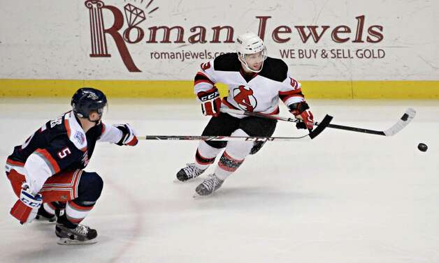 Hartford Wolfpack's #5 Tommy Hughes, left, and Albany Devils' #9 Joe Whitney chase an airborne puck during Saturday's game at the Times Union Center April 18, 2015 in Albany, NY.  (John Carl D'Annibale / Times Union) Photo: John Carl D'Annibale / 00030124T