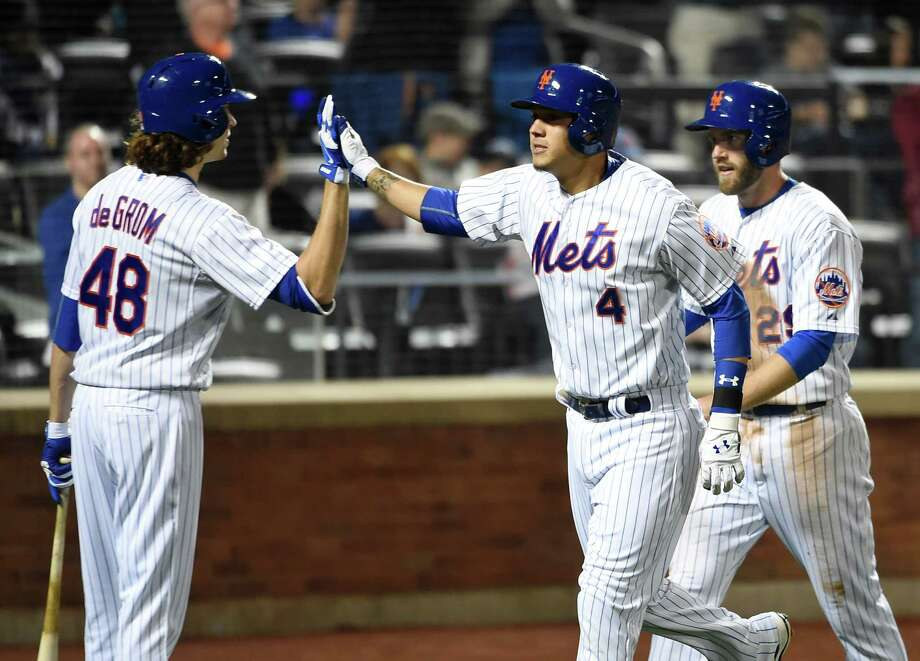 New York Mets' Wilmer Flores (4) and Eric Campbell (29) are greeted at home plate by Jacob deGrom (48) after Flores hit a two-run home run off Miami Marlins starting pitcher Jose Urena that also scored Campbell in the sixth inning of a baseball game at Citi Field on Saturday, April 18, 2015, in New York. (AP Photo/Kathy Kmonicek) ORG XMIT: NYM116 Photo: Kathy Kmonicek / FR170189 AP