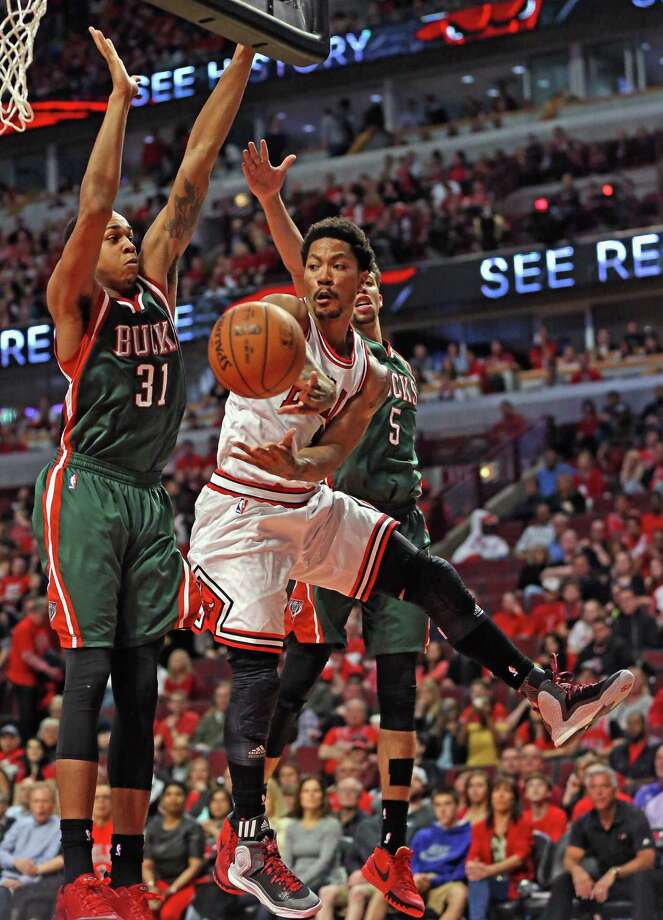 CHICAGO, IL - APRIL 18: Derrick Rose #1 of the Chicago Bulls leaps to pass under pressure from John Henson #31 and Michael Carter-Williams #5 of the Milwaukee Bucks during the first round of the 2015 NBA Playoffs at the United Center on April 18, 2015 in Chicago, Illinois. The Bulls defeated the Bucks 103-91. NOTE TO USER: User expressly acknowledges and agress that, by downloading and or using the photograph, User is consenting to the terms and conditions of the Getty Images License Agreement. (Photo by Jonathan Daniel/Getty Images) ORG XMIT: 548980001 Photo: Jonathan Daniel / 2015 Getty Images