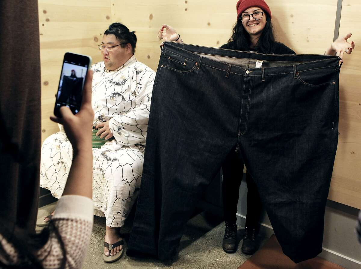 Levi's employee Liz Valashinas poses with pants that were a close fit for retired sumo wrestler Yamamotoyama Ryuta (AKA: Yama) in the Levi's store on Market Street in San Francisco, Calif., Saturday April 18, 2015.