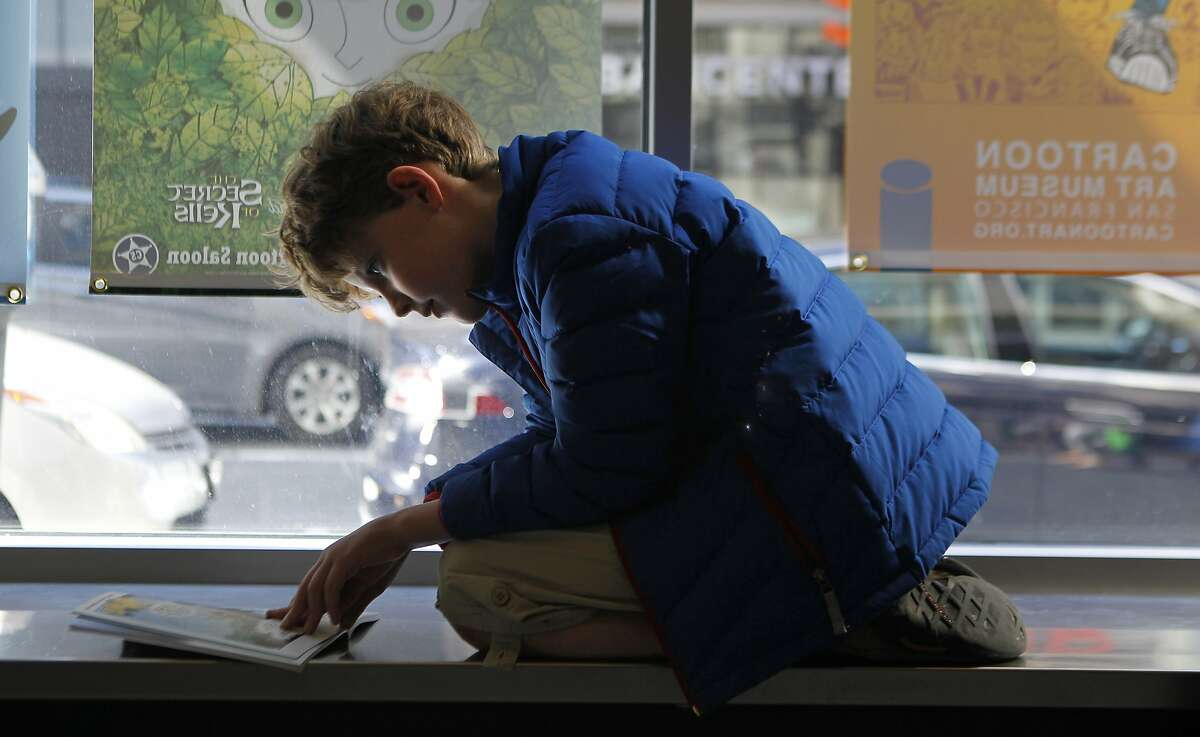 Quin Brewer, 10, of Marin reads a comic book in the window of the Cartoon Art Museum in the South of Market district of San Francisco, Calif. Saturday, April 18, 2015.