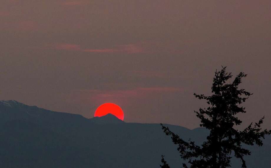 A sun tinted red by grass fires in Siberia sets behind the Olympic Mountains on Saturday, April 18, 2015. Photo: DANIELLA BECCARIA, SEATTLEPI.COM / SEATTLEPI.COM