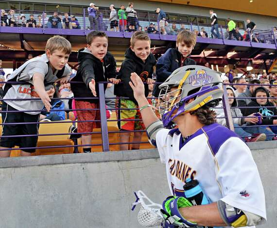 UAlbany's #17 Adam Osika high fives members of the Bethlehem youth lacrosse team, from left, Evan Diligent, Eamonn Hayes, Rylan Gaffney and Henry Lane before Saturday's game against Yale April 18, 2015 in Albany, NY.  (John Carl D'Annibale / Times Union) Photo: John Carl D'Annibale / 00031486A