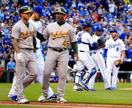KANSAS CITY, MO - APRIL 18:  Brett Lawrie #15 of the Oakland Athletics walks toward first base after being hit by a pitch by pitcher Yordano Ventura #30 of the Kansas City Royals during the 4th inning of the game against the Kansas City Royals at Kauffman Stadium on April 18, 2015 in Kansas City, Missouri.  (Photo by Jamie Squire/Getty Images)