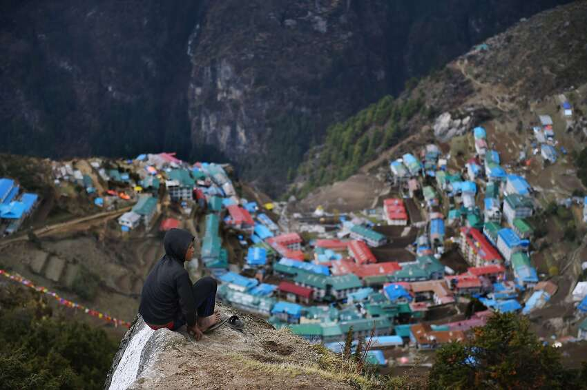 Nepali porter Milan Rai, 14, rests as he makes his way up a rocky path high above the north-eastern town of Namche Bazar on his way to making a delivery to a hotel in a nearby town at higher elevation on April 18, 2015. Today, Rai was carrying sacks of flour but he and others like him ferry goods between towns for a living. Rai said he makes around 3,000 Nepalese Rupees (30 USD) a month. Namche Bazar, seen in the background, is a usual stop for trekkers and climbers heading to the upper reaches of the Kumbhu region, which is home to Mount Everest.