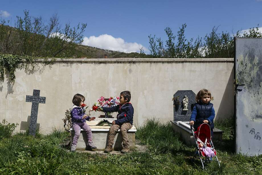 A boy gives a flower to a girl while sitting on a tomb, as another girl pushes a toy stroller at a cemetery in the small northern village of Valdenoceda, Spain, Saturday, April 18, 2015. Photo: Daniel Ochoa De Olza, Associated Press